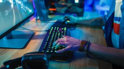 Close-Up Hands Shot Showing a Gamer Using the Keyboard while Playing an Online Shooter Video Game. Keyboard has Green Neon Lights in Buttons. Gamer is Wearing a Bracelet. Room is Dark.