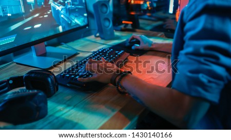Close-Up Hands Shot Showing a Gamer Using the Keyboard while Playing an Online Shooter Video Game. Keyboard has Led Neon Lights in Buttons. Gamer is Wearing a Bracelet. Room is Dark.
