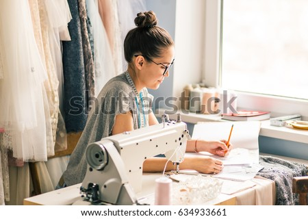 Shutterstock Close up. hands woman Tailor working cutting a roll of fabric on which she has marked out the pattern of the garment she is making with tailors chalk.