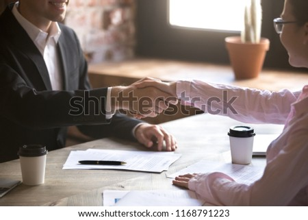 Close up handshake of two successful businesspeople after good deal in the office. Good first impression, making acquaintance concept