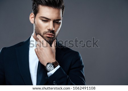 Close-up handsome and successful man in an expensive suit. He is in a white shirt with a tie. A strong, stylish successful man in a suit posing.