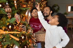 Close up happy African American parents with adorable little son decorating Christmas tree, smiling mother and father holding basket with balls and baubles, enjoying winter holidays together