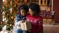 Close up happy African American woman with adorable daughter opening Christmas gift box, sitting on floor near festive tree at home, smiling mother and little girl hugging, unpacking present