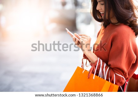 Close up happy Asian pretty girl holding shopping bags while using smartphone background shopping mall concept. #1321368866