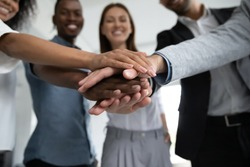 Close up happy diverse business people putting hands together, showing support and unity. Multiracial colleagues involved in team building activity. Staff training concept, start working together.