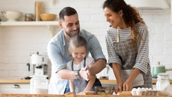 Close up happy father clapping hands with flour hugging daughter near mother looking at husband in kitchen at home. Smiling couple with child playfully cooking dinner with baking pastry.