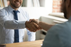 Close up happy two business men shaking hands, coming to agreement after negotiations meeting. Smiling employer welcoming job applicant at interview in office, making offer, recruitment concept.