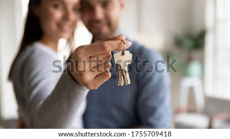 Close up happy woman hugging man, holding keys from new first house, young family celebrating moving day, satisfied customers couple purchase real estate, mortgage and relocation concept Stockfoto ©