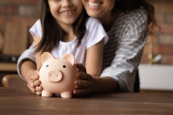 Close up happy young mother and adorable little daughter holding touching pink piggy bank, caring mum and adorable girl child saving money for future, family insurance and investment concept