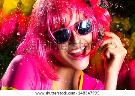 Close up Happy Young Party Girl Wearing Dark Pink Wig, Shades and Shirt on a Water Splash, with Toothy Smile Expressing Happiness. #148347995