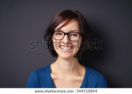 Shutterstock Close up Happy Young Woman, Wearing Eyeglasses, Showing Toothy Smile at the Camera Against Gray Wall Background.