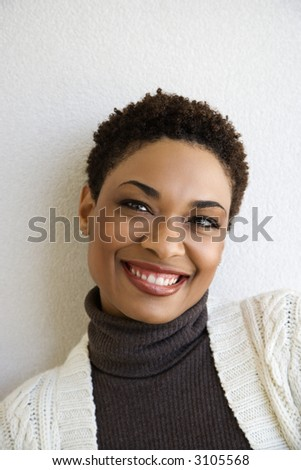 Close up head and shoulder of African- American woman standing against white wall smiling looking at viewer.