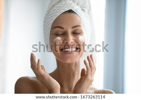 Close up head shot beautiful lady laughing while applying skincare moisturizing creme after morning showering. Happy young woman with wrapped in towel head enjoying smoothing skin, domestic routine. Photo stock ©