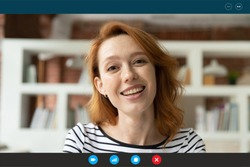 Close up head shot beautiful smiling young red-haired woman holding distant video call conversation, communicating online with friends or family, enjoying remote quarantine lifestyle workday.