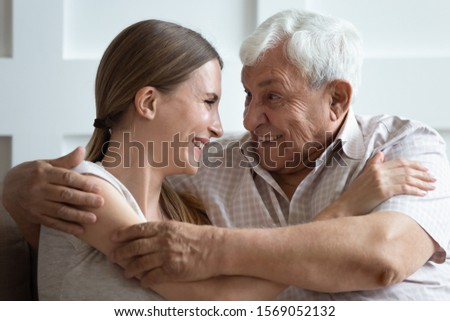 Close up head shot bonding two generations family embracing, enjoying sweet tender moment at home. Happy young woman communicating, chatting with pleasant smiling 70s father, sitting on couch. Stockfoto ©