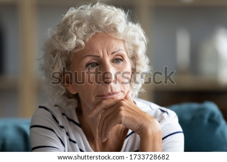 Close up head shot elderly mature woman lost in thoughts, sitting alone on sofa indoors. Unhappy middle aged grandmother suffering from depression, thinking of personal psychological problems.