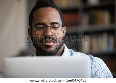 Close up head shot focused young african ethnicity man in glasses looking at laptop screen, involved in project work. Concentrated skilled millennial biracial man analyzing marketing statistics.