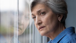 Close up head shot frustrated middle aged 60s woman standing near window, looking in distance, feeling depressed indoors. Unhappy mature senior lady suffering from personal problems or loneliness.