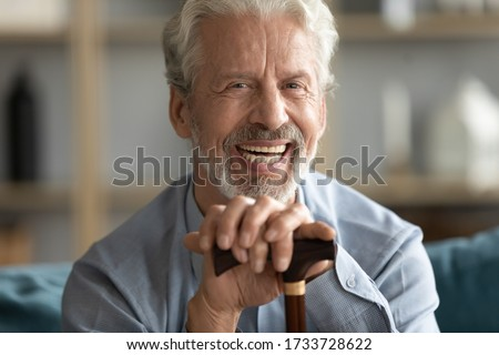 Close up head shot happy disabled mature older grandfather relaxing on sofa with walking cane, feeling excited of good news. Portrait of laughing positive middle aged retired man looking at camera.