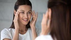 Close up head shot happy female client satisfied with eyes area condition after beauty spa procedure, looking in mirror at bathroom. Smiling pretty brunette woman moisturizing face skin in morning.