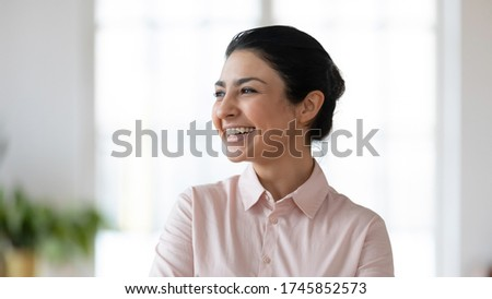 Close up head shot laughing young indian businesswoman looking away. Happy smiling millennial hindu ethnicity employee planning future job, thinking of new challenges opportunities in office.