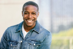 Close up head shot of a handsome commercial african american model with perfect white teeth smile after dentist, dental and orthodontic advertisement