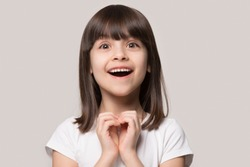 Close up head shot portrait cheerful excited small 6 years old girl looking at camera, showing heart gesture, isolated in grey studio background. Overjoyed cutie feeling happy achieving wished goal.