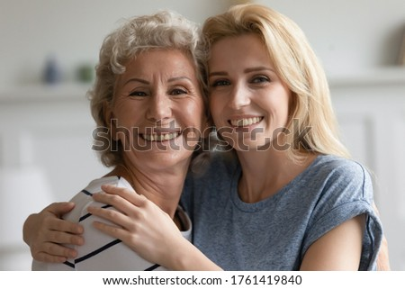 Close up head shot portrait elderly grandmother and grown up adult blond granddaughter hugging smiling looking at camera. Concept of multi generational family warm relations protection caress and love