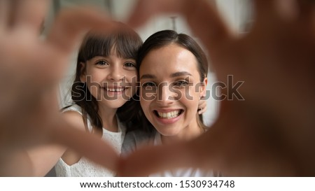 Close up head shot portrait happy family of two making heart gesture, focus on smiling young mother bonding little cute daughter. Overjoyed small girl showing love sign with millennial mommy.
