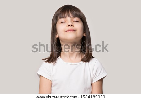 Close up head shot portrait image with relaxed little brown-haired girl, reduce stress. Wellbeing concept rest kid meditating and deep breathing on gray background, six year child with eyes closed