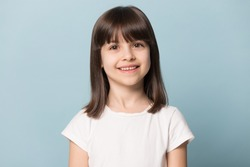 Close up head shot portrait image with smiling little brown-haired girl. Concept happy and beauty kid with good healthy teeth for dental on blue background, six year child looking at camera and posing