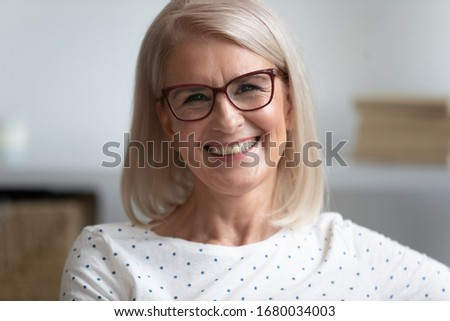 Close up head shot portrait of smiling attractive middle aged woman in eyeglasses. Happy older female teacher with toothy smile recording educational video, giving remote professional consultation.