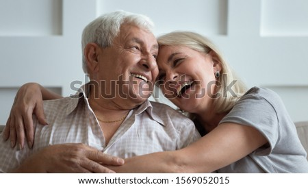 Close up head shot portrait overjoyed middle aged woman cuddling happy older grey haired 80s father at home. Laughing married family couple chatting, enjoying free weekend time together at home.