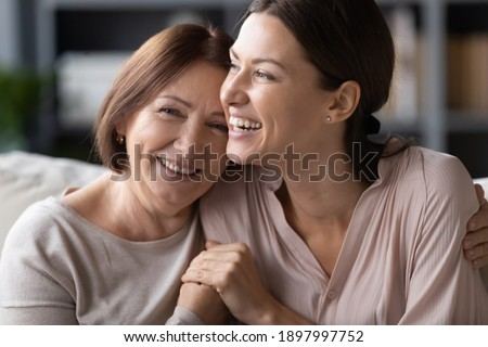 Close up head shot portrait smiling mature mother and grownup daughter cuddling, family enjoying tender moment, happy young woman with elderly mum hugging, spending leisure time together