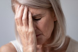 Close up head shot portrait unhealthy middle aged woman touching forehead. Unhappy sad mature female retiree feeling tired, suffering from head ache, migraine or dizziness, healthcare concept.