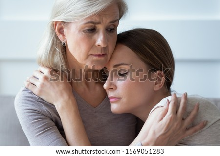 Close up head shot sad mature grey haired mother embracing, comforting upset adult daughter, sitting together on sofa. Unhappy young woman supporting stressed middle aged mommy, experiencing grief.
