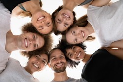 Close up head shot smiling beautiful mixed race people touching heads in circle, looking down at camera, healthy multiracial young teammates in sportwear feeling excited, waiting for training workout.