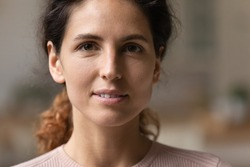 Close up head shot view attractive young 30s authentic woman with perfect skin looking at camera. Portrait of happy pleasant millennial caucasian hispanic latin confident lady with natural beauty.