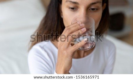 Close up head shot young mixed race woman drinking glass of fresh pure water, sitting on bed at home. Responsible biracial girl taking care of health, preventing dehydration. Good daily habit concept.
