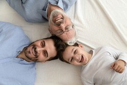 Close up head to head above view three cheerful faces looking pose for camera grandfather grown up son and little adorable grandkid, different multi generational beautiful men family portrait concept