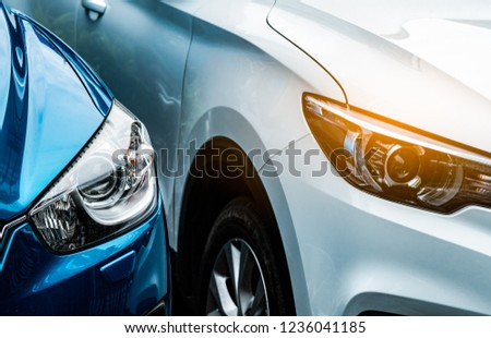 Close up headlamp light of blue and white SUV car. Blue car parked beside white car. Automotive industry concept. Electric or hybrid auto concept. Car service. Road trip adventure. Automobile rental. #1236041185