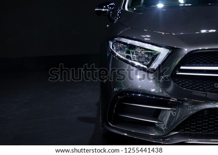 close up headlights front side view , black color car in room .