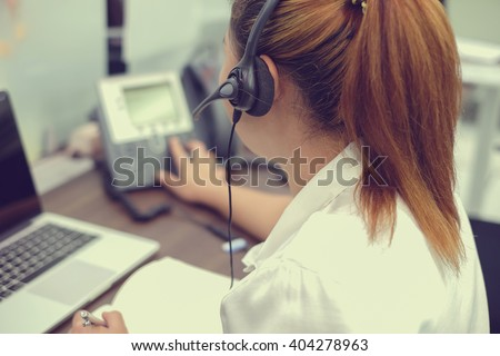 close up headphone asian girl response answer customer or partner in operation room for business and technology concept.