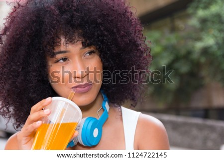 Close up headshot of beautiful young student tourist girl drinking orange juice with headphones. Blurred trees in background. She is black, on her early twenties, Afro style frizzy hair. #1124722145