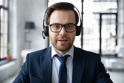 Close up headshot portrait of male CEO or director in headphones talk speak on video call in office with business client. Caucasian businessman wear earphones have webcam digital virtual conference.