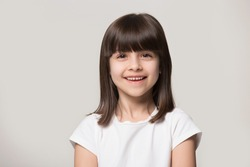 Close up headshot portrait of smiling little girl isolated on grey studio background look at camera, happy small preschooler child in white t-shirt posing feel overjoyed excited show healthy teeth