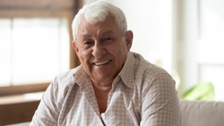 Close up headshot portrait of smiling mature man sit on couch at home look at camera posing, happy senior male feel optimistic uplifted demonstrate healthy positive elderly lifestyle concept
