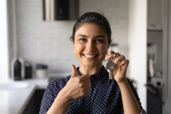 Close up headshot portrait of smiling young Indian woman show keys buy first own house. Profile picture of excited ethnic female renter tenant show thumb up recommend real estate agency good service.