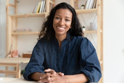 Close up headshot portrait picture of happy african american businesswoman sitting by table. Smiling attractive young diverse woman mentor looking at camera in coworking office.
