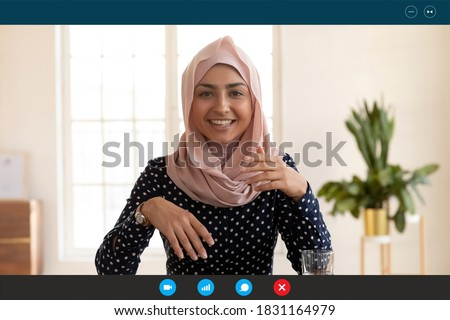 Close up headshot screen view of smiling Indian woman in hijab have webcam digital virtual conference on computer online. Happy ethnic female talk speak on video call with client or customer.